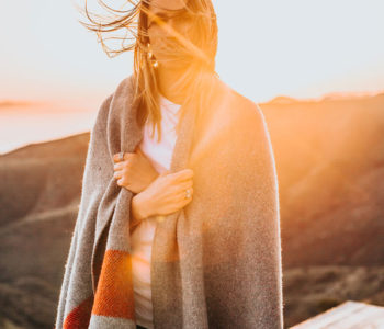Woman standing with a blanket around her.