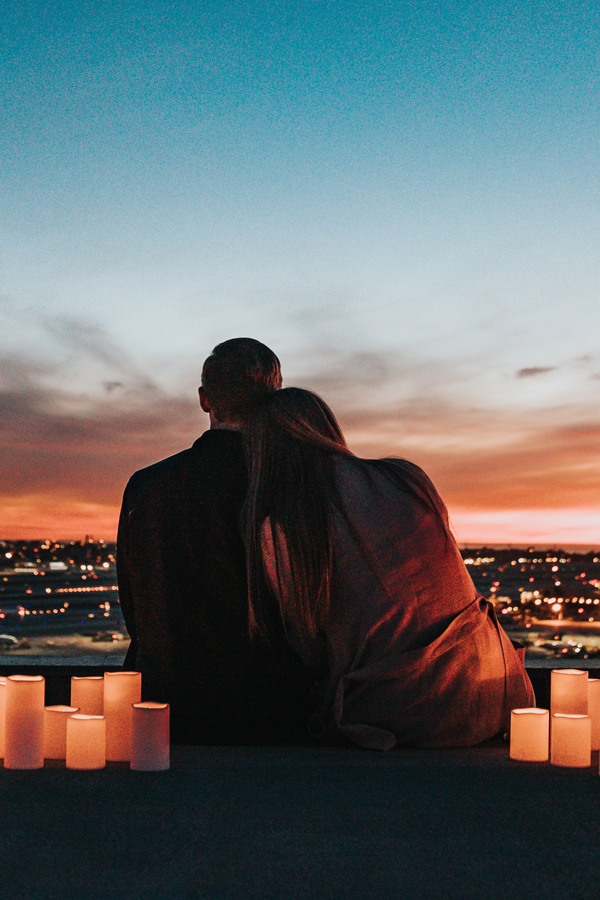 Couple hugging at sunset surrounded by candles, facing away from the camera.