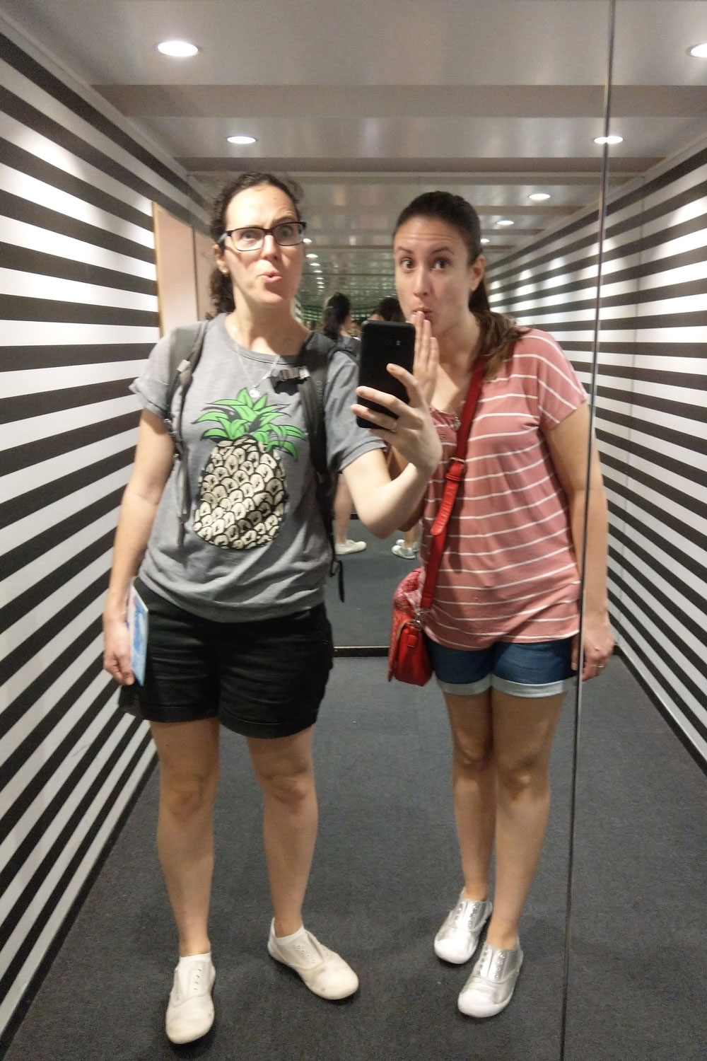 Two people standing in front of mirror.