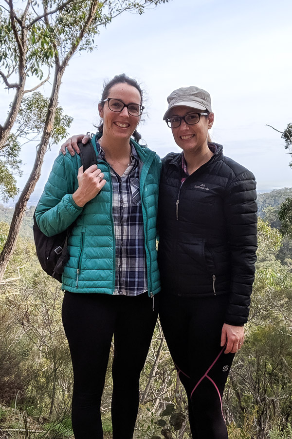 Two women standing in hiking gear surrounded by trees.
