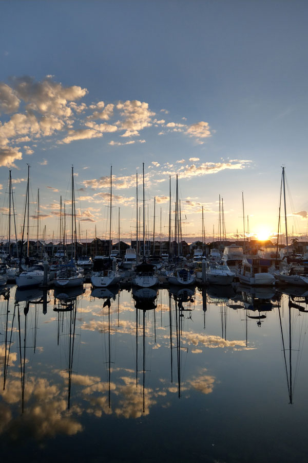Sun setting behind yachts moored in a marina with clouds in the sky.
