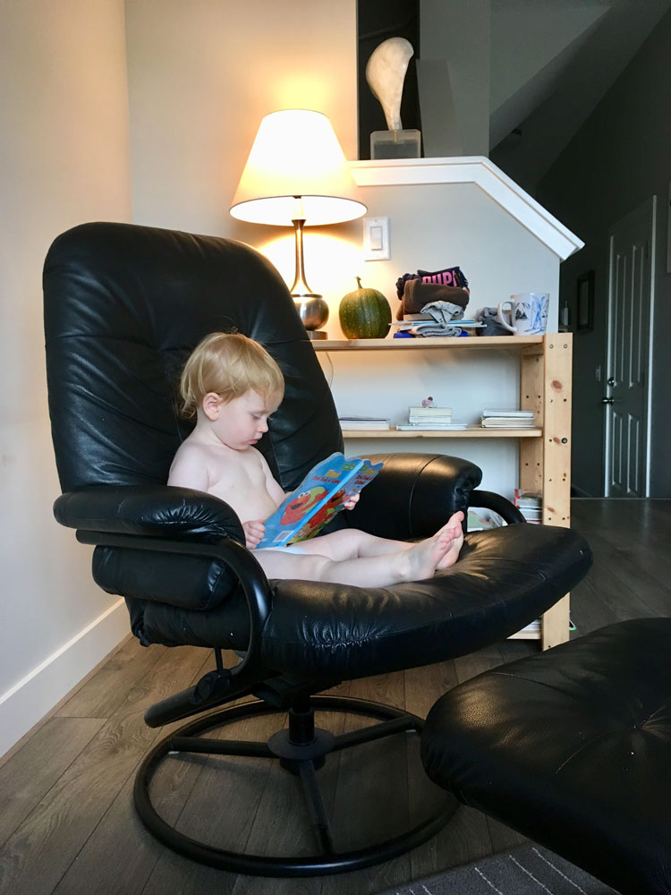 Toddler reading a book in a chair.