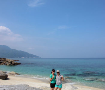 Two girls standing on tropical island beach.