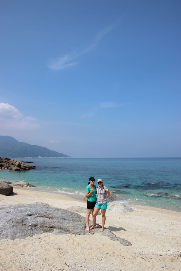 Two girls standing on tropical island beach.