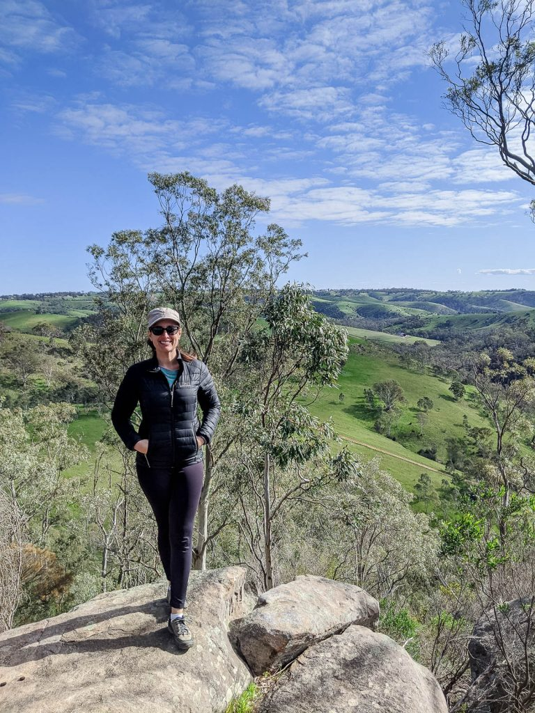 Woman standing on a rock with view of hills and blue sky in background.
