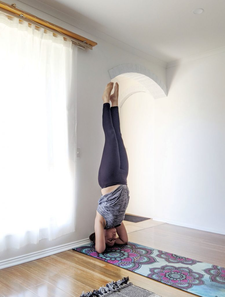 Laura doing a headstand on her yoga mat.