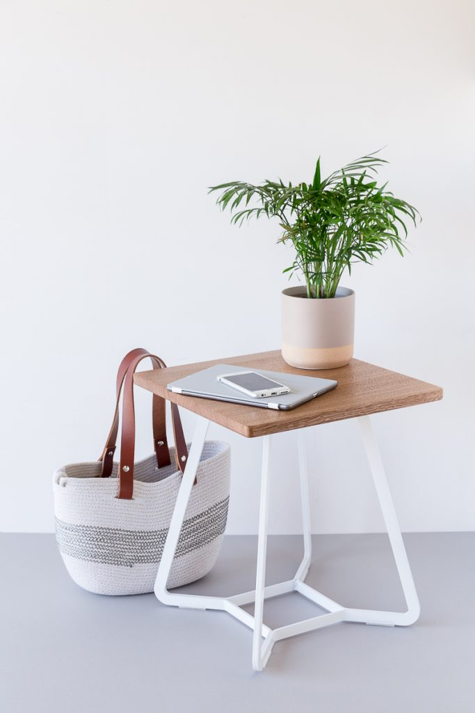 An iPhone and iPad on a table next to a pot plant and rope bag.