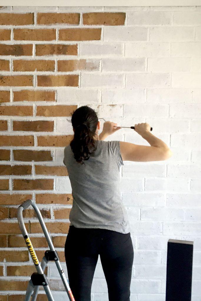 Sarah painting a brown brick wall white.