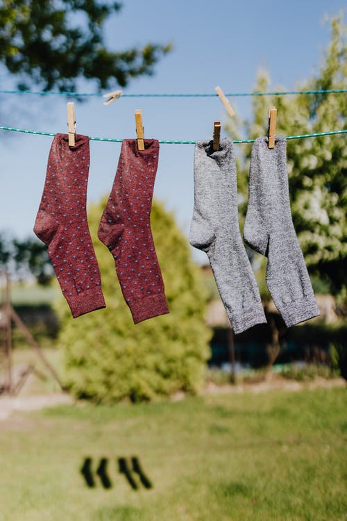 Two pairs of socks hanging on a line.
